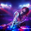 Disc jockey playing music with light beam effects on stage — Stock Photo #50330945