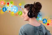 молодая женщина, слушать музыку с наушниками — Стоковое фото