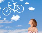 Genç kız mavi gökyüzü üzerinde bisiklet bulutlar bakarak — Stok fotoğraf