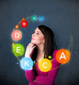 Young woman thinking with vitamins circulation around her head — Stock Photo