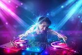 Energiska dj blandande musik med kraftfulla ljuseffekter — Stockfoto