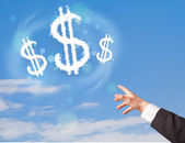 Hand pointing at dollar sign clouds on blue sky  — Stock Photo