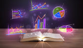 Book on wooden deck with glowing graph illustrations — Stock Photo