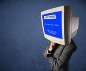 Persona con una testa di monitor e la schermata blu di errore irreversibile sulla di — Foto Stock