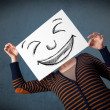 Woman with drawed smiley face on a paper in front of her head — Stock Photo #50774083