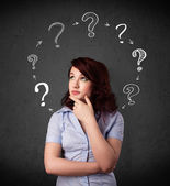 Young woman thinking with question mark circulation around her h — Stock Photo