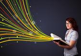 Ganska ung kvinna läser en bok medan färgglada linjer comin — Stockfoto