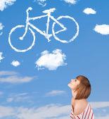Jeune fille voir les nuages de la bicyclette sur le ciel bleu — Photo