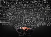 Businessman sitting in front of a blackboard with charts — Stock Photo