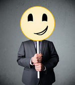 Businessman holding a smiley face emoticon — Stock Photo