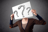 Woman holding paper with drawed question marks in front of her h — Stock Photo