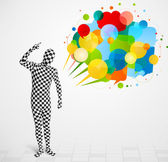 Strange guy in morphsuit looking at colorful speech bubbles — Stock Photo