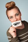Хорошенькая молодая девушка держит белая карточка с улыбкой рисунок — Стоковое фото