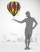 man in full body suit holding balloon — Stock Photo