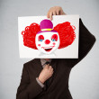 Businessman holding a cardboard with a clown on it in front of h — Stock Photo #51498639