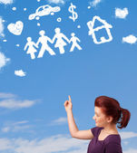 Young girl daydreaming with family and household clouds — Stock Photo