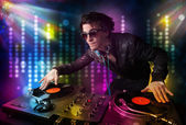 Dj playing songs in a disco with light show — Stock Photo