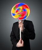 Businessman holding a lollipop — Stock Photo