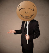 Businessman holding a smiley face board — Stock Photo