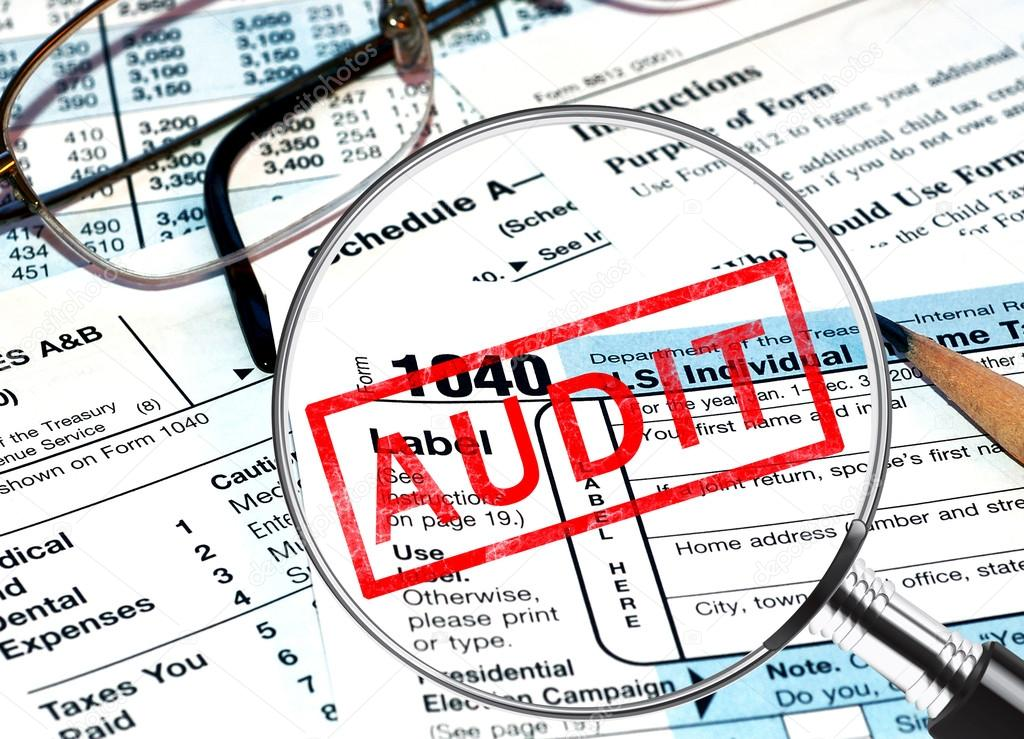 Tax forms under a magnifying glass revealing a tax audit — Stock Photo #13408462