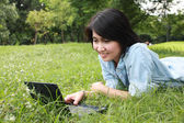 A smiling young girl with laptop outdoors — Stockfoto