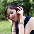 Beautiful girl listening music in the park — Stock Photo #28192351