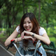 Woman with a bike outdoors smiling — Stock Photo #28541361