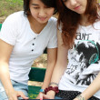Two beautiful  girls with laptop on natural background  — Stock Photo
