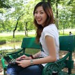 young pretty woman with laptop siting on the bench in a park — Stock Photo