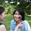Beautiful girls helping their friend to makeup — Stock Photo #28541565
