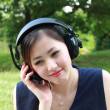 Beautiful girl listening music in the park — Stock Photo #28541613