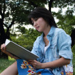 Beautiful young woman writing outdoors in a park — Stock Photo