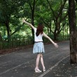 Young woman walking on path in city park  — 图库照片