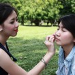 Beautiful girls helping their friend to makeup — Stock Photo