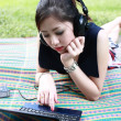 Girl with a laptop and headphones at the park  — Stock Photo