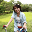 Woman with a bike outdoors smiling  — Stock Photo