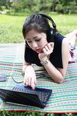 Mädchen mit einem laptop und kopfhörer im park — Stockfoto