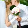Bride and groom with a bouquet of kisses — Stock Photo #8612630