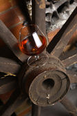 Glass of brandy on wooden wheel — Stock Photo
