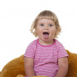 A child sits on a soft toy on a white background — Stock Photo