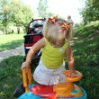 Little girl driving her toy car in the park, outdoors — Stockfoto