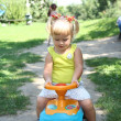Little girl driving her toy car in the park, outdoors — Stock Photo