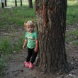 Cute little blonde girl near a tree — Stock Photo #30147591