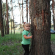 Cute little blonde girl near a tree — Stock Photo #30147597