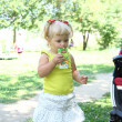 Blond little girl drinking juice with straw — Stok fotoğraf