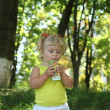 Blond little girl drinking juice with straw — Stock fotografie