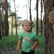 Cute little blonde girl near a tree — Stock Photo