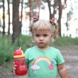 Little girl drinking from plastic bottle — Stock Photo