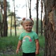Cute little blonde girl near a tree — Stock Photo #30147673