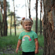 Stock Photo: Cute little blonde girl near a tree